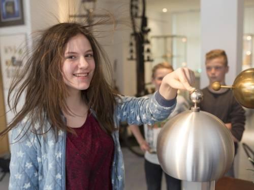 Einem Mädchen stehen bei einem elektrischen Experiment die Haare zu Berge