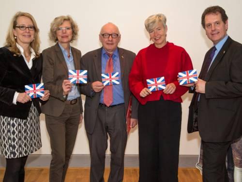 Drei Frauen und zwei Männer mit England-Postkarten in der Hand.