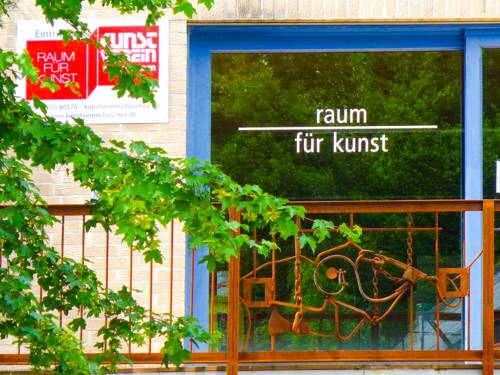 Gläserne Eingangstür mit dem Schriftzug Raum für Kunst.