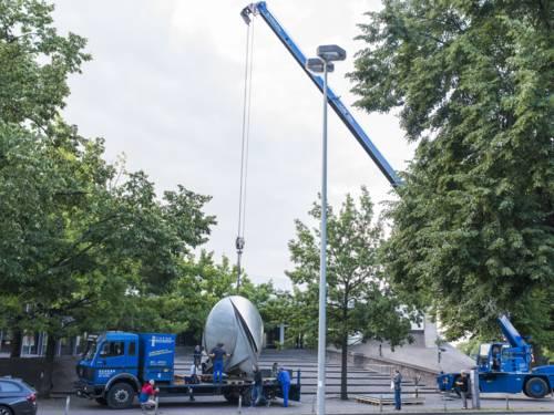 Eine runde 3,5 Meter hohe Stahlskultur hängt an einem Stahlseil eines Lastenkrans und wird auf die Transportfläche eines LKWS abgesenkt. Dabei sichern vier Männer das Objekt.
