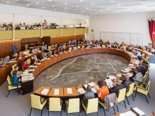 Saal mit elipsenförmig angebrachtem Tisch, an dem Menschen sitzen