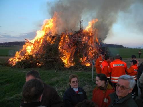 Feuerwehrmänner und Menschen vor einem lodernden Osterfeuer