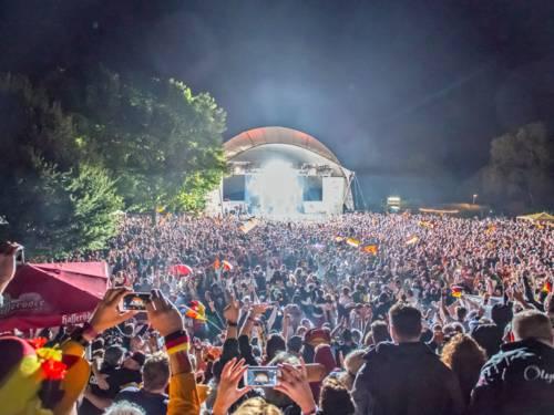 Menschenmenge in Fußballfankleidung vor einer Open-air-Bühne