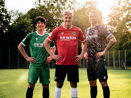 Drei Fußballspieler in Trikots von Hannover 96