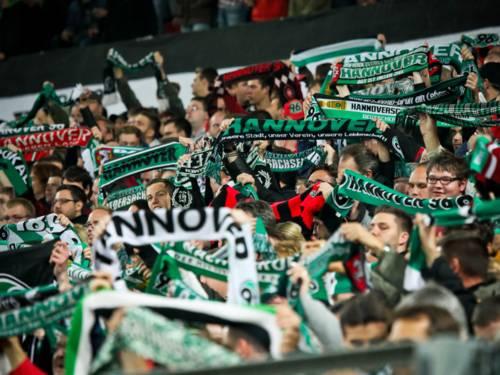 """Fußballfans im Stadion halten Schals mit der Aufschrift """"Hannover 96"""" in die Höhe."""