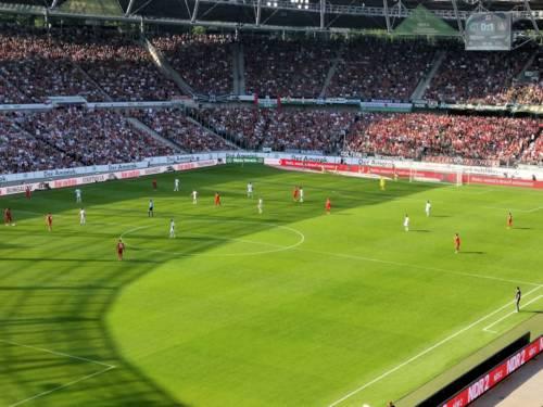 Blick in gefülltes Stadion mit Fußballspielern auf dem Feld