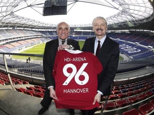 Zwei Männer stehen in einer Arena und halten ein Fußballtrikot in den Händen.
