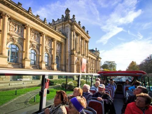 Ein Bus fährt an einem großen Gebäude vorbei.