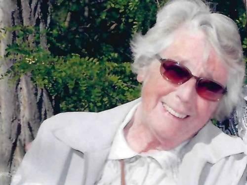 Lächelnde Frau mit weißem Haar und Sonnenbrille
