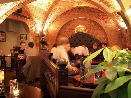 Menschen sitzen an Tischen in einem Raum mit Kreuzgewölbe.