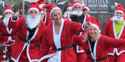 Laufende Männer und Frauen in Weihnachtsmannkostümen.
