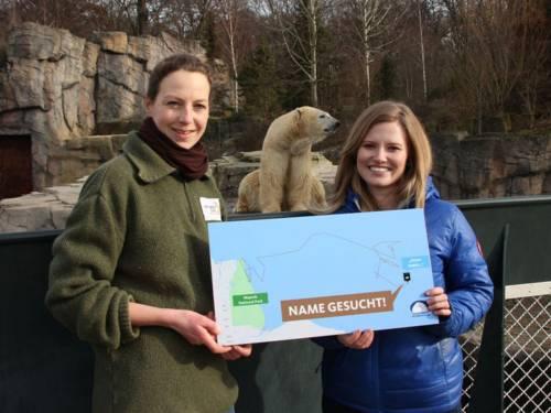 """Zwei Frauen mit einem Schild mit der Aufschrift """"Name gesucht"""", im Hintergrund ein Eisbär"""