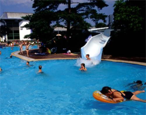 Kinder im Wasser, ein Kind kommt gerade die weisse Wasserrutsche hinuntergesaust, im Vordergrund ein Mädchen mit Schwimmreifen