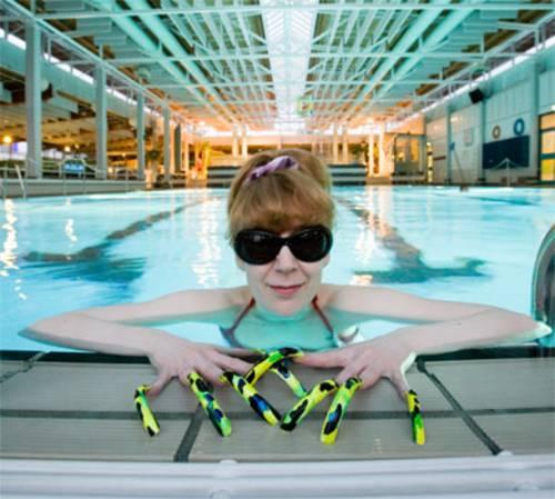 Eine Frau mit großer Sonnenbrille und sehr langen, bunt lackierten Nägeln lehnt sich an den Beckenrand vom Schwimmerbecken.