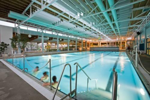 Blick auf das fast leere, beleuchtete Schwimmerbecken, drei Badende lehnen sich gegen den Beckenrand
