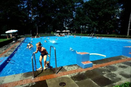 Ein Mädchen an der Stahlleiter ins Schwimmbecken, Menschen im Wasser, Auf den grünen Liegewiesen weisse Sonnenschirme