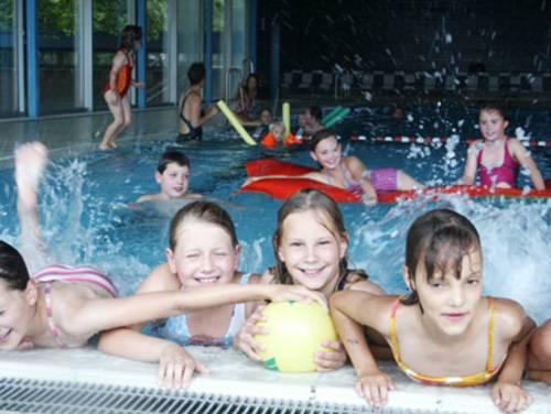 Vier Mädchen mit gelben Ball am Beckenrand, im Hintergrund im Wasser tobende Kinder
