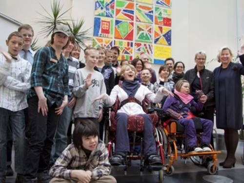 Mehrere Schüler einer Förderschule, zwei von ihnen im Rollstul, die vor einem selbstgemalten Kunstwerk stehen und fröhlich in die Kamera winken.