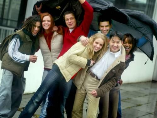 Junge Leute posieren im Regen für ein Gruppenfoto.