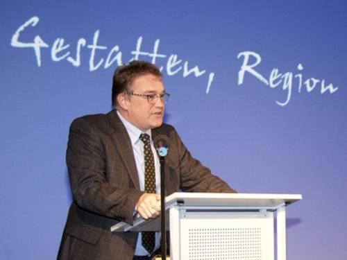 """Der Regionspräsident an einem Rednerpult. Hinter ihm an der Wand ist ein Teil eines Schriftzugs zu sehen """"Gestatten, Region"""""""
