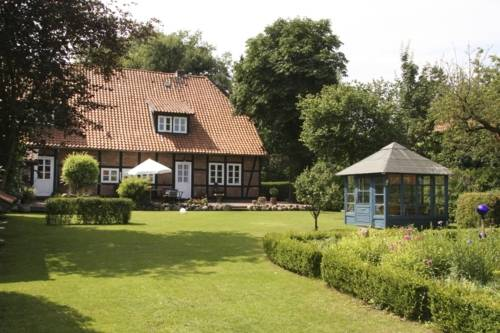 Gepflegtes, parkähnliches Grundstück mit Rasen und Hecken, im Hintergrund ein rotes Fachwerkhaus im Sonnenschein
