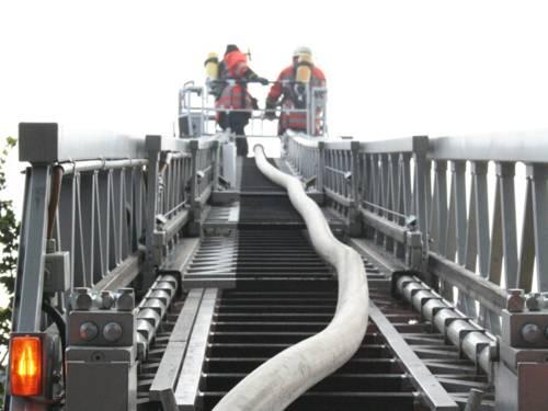 Zwei Feuerwehrmänner stehen auf einer ausgefahrenen Feuerwehrleiter mit dem Rücken zur Kamera.