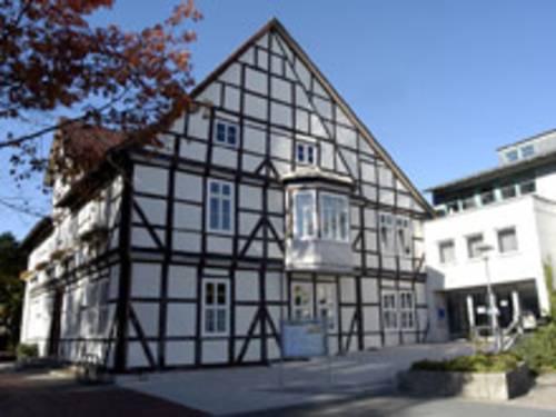 Fachwerkhaus mit weißen Fenstern und einem weißen Erker im ersten OG. Rechts am Fachwerkhaus befindet sich ein moderner Anbau in Kubusform.