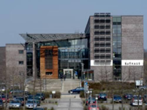 Großer moderner Gebäudekomplex mit Glas und Holzelementen. Davor befindet sich ein Parkplatz.
