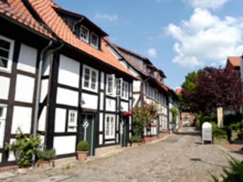 Links im Bild befinden sich aneinandergereihte Fachwerkhäuser. Teilweise sind Pflanzen vor den Häusern. In der Mitte des Bildes ist eine Straße aus Kopfsteinpflaster.