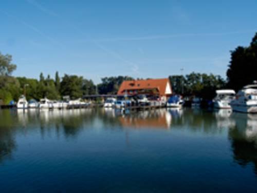 Wasserfläche mit Blick auf einen Yachthafen. Der Hafen wird durch Baumbestand eingerahmt. In der Mitte des Hafens befindet sich ein Haus mit rotem Satteldach.