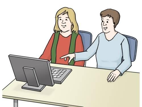 Eine Person erklärt etwas am Computer.