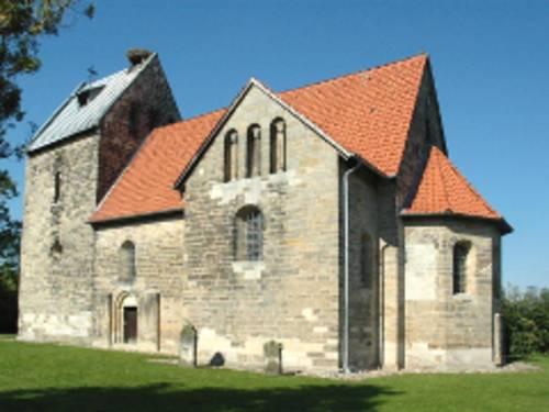 Blick von außen auf ein romanisches Kirchengebäude.