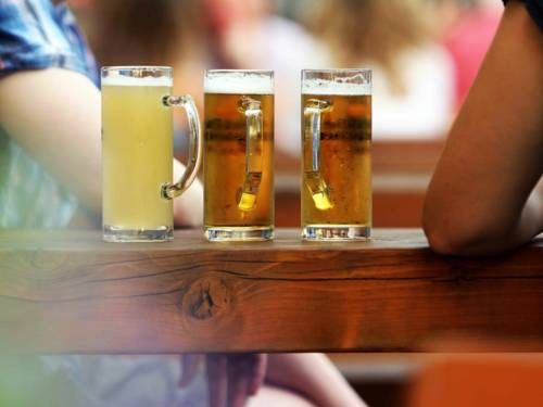 Drei Gläser Bier auf einem Holzbalken.