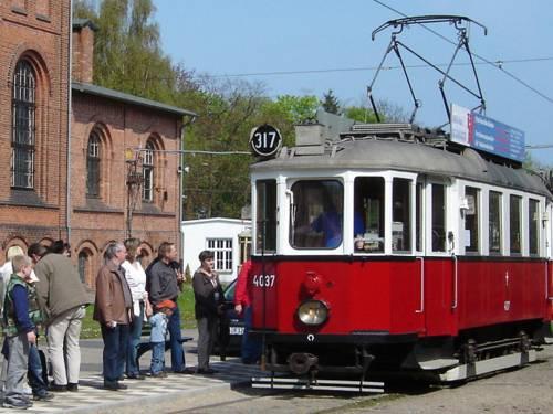 Historischer Straßenbahnwagen an einer Haltestelle. Personen stehen an um einzusteigen.