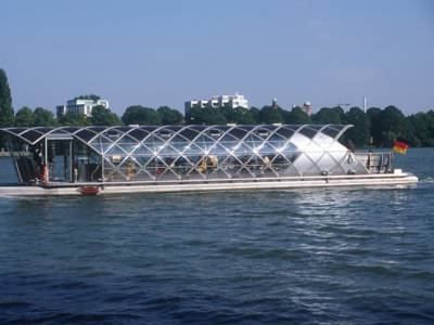 Boot mit Glasdach auf einem Gewässer, im Hintergrund Bäume und mehrstöckige Häuser