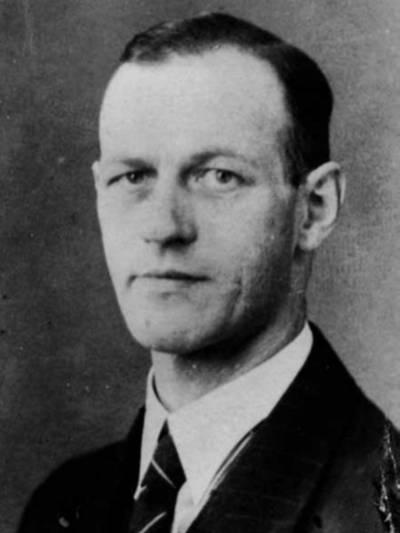 Alte Portraitaufnahme (schwarz-weiß) eines Mannes im Anzug.