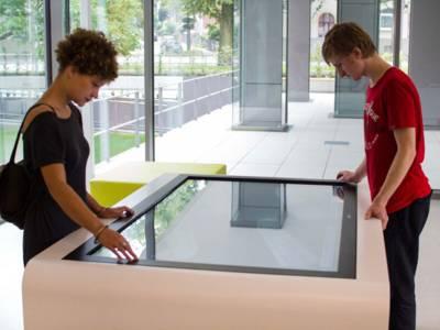 Eine junge Frau links an einem Medientisch und rechts ein junger Mann.