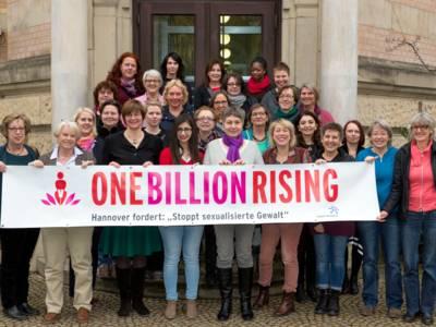 """28 Frauen stehen auf einer Treppe und schauen in die Kamera, die Frauen in der vordersten Reihe halten ein Banner, darauf steht: """"ONE BILLION RISING. Hannover fordert: 'Stoppt sexualisierte Gewal'"""""""