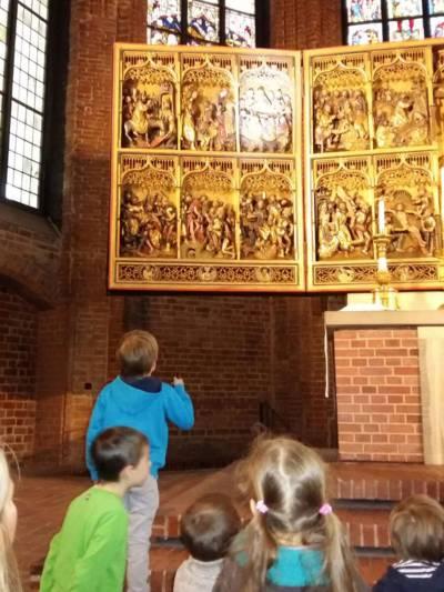 Mehrere Kinder in einer Kirche, die sich den Altarbereich anschauen.