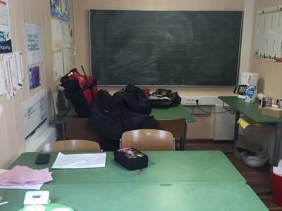 Der Schulwagen von Innen mit Tischen, Stühlen und einer grünen Tafel. Die Wände sind beklebt mit Zeichnungen, Bastelarbeiten und Unterrichtsmaterialien.