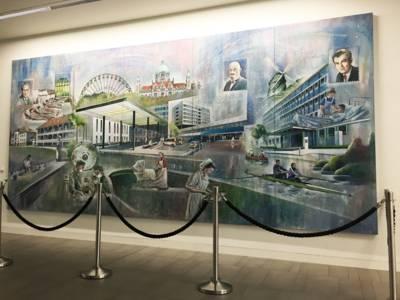 Ein sehr großes Gemälde, das aktuelle und geschichtliche Impressionen zeigt. Vor der Wand ist eine Absperrung aufgebaut. In der Mitte des Bildes ist ein Abspielsymbol abgebildet.