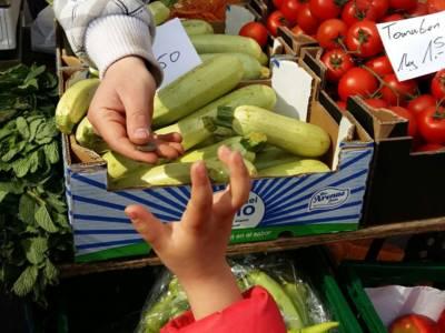 Die Hand eines Kindes, das an einem Gemüsestand steht, nimmt vom Händler Wechselgeld entgegen.