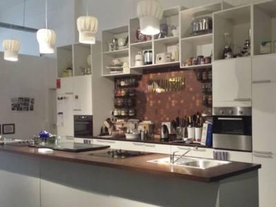 Eine Küche mit Kochinsel. Die vier Lampen an der Decke sehen aus wie Kochmützen. In der Mitte des Bildes ist ein Abspielsymbol abgebildet.