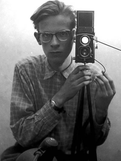 Ein Mann mit Brille und im Hemd hinter einer Kamera auf einem Stativ.