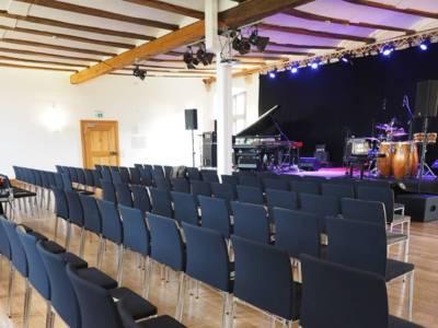 Ein großer Saal in einem Schloss, der als Veranstaltungsraum genutzt wird. Rechts ist eine erhöhte Bühne, auf der Musikinstrumente stehen. Vor der Bühne sind mehrere Stuhlreihen aufgebaut.