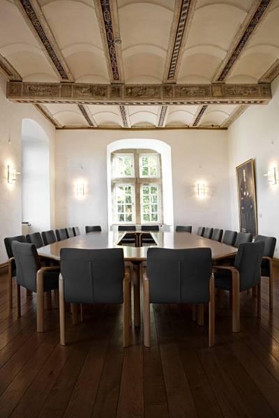 Ein lichtdurchfluteter Saal in einem Schloss mit einem großen Besprechungstisch, andem zwanzig Stühle stehen.