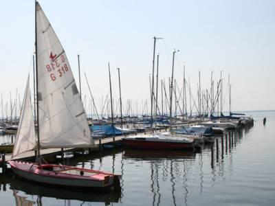 Steg mit Segelbooten, das erste Boot hat gesetzte Segel
