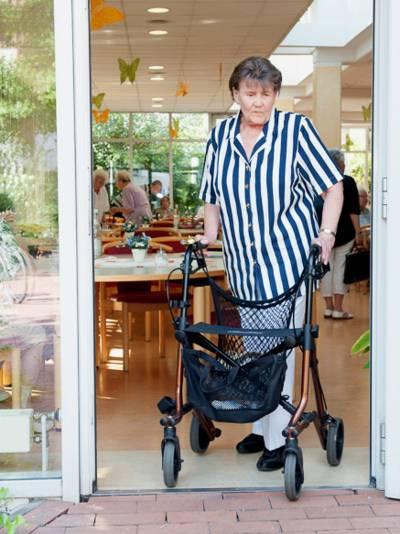 Eine ältere Frau schiebt einen Rollator durch eine Terrassentür.