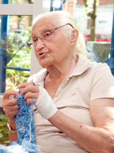 Eine ältere Dame strickt.