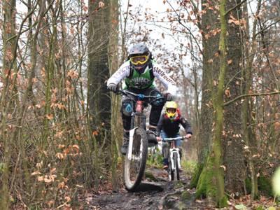Zwei Mountainbiker tragen Schutzkleidung und fahren hintereinander über einen unebenen Weg mit zahlreichen Baumwurzeln.